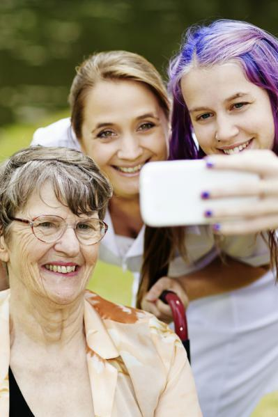 Woman in wheelchair, female support worker and young woman pose for a selfie