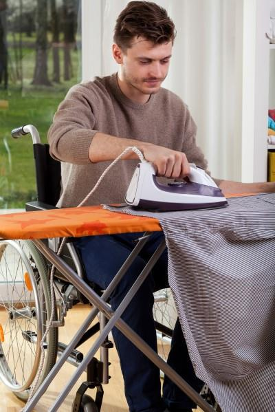 Young man in wheelchair ironing clothes