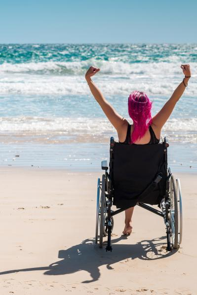 Young woman in wheelchair on the beach celebrating the view