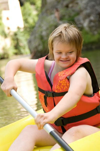 Young woman with a disability paddling in a kayak